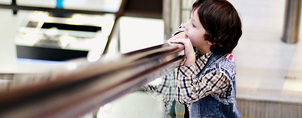 enfant regardant par dessus un garde-corps en verre